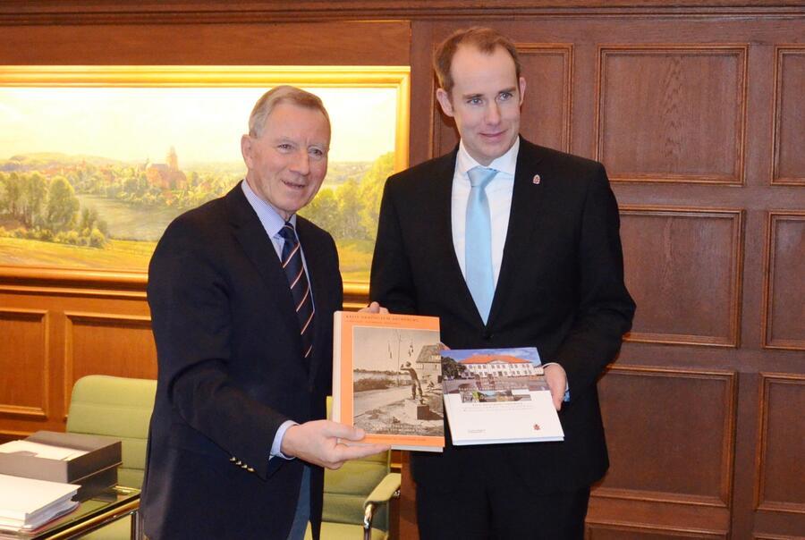 Kreispräsident Meinhard Füllner und Landrat Christoph Mager mit der ersten und der neuen Ausgabe des Bildbandes
